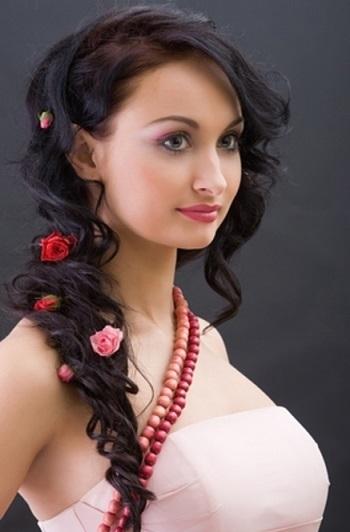 Зачіска в українському стилі на фото, прикрашена квітами.